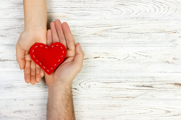 Help, heart in hand on wood background. valentine day concept. copy space