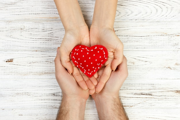 Help, heart in hand on wood background. valentine day concept