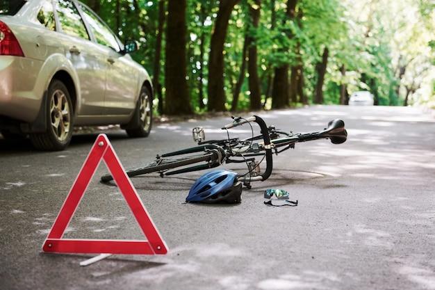 Помощь уже в пути. велосипед и серебряная автомобильная авария на дороге в лесу в дневное время