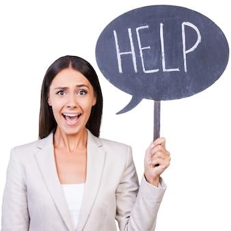 도와 줘요! 흰색 배경에 고립 된 서있는 동안 도움말 텍스트와 함께 배너를 들고 formalwear에서 아름 다운 젊은 여자