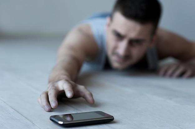 도와 줘요! 좌절된 젊은이 바닥에 누워 휴대 전화에 손을 기지개