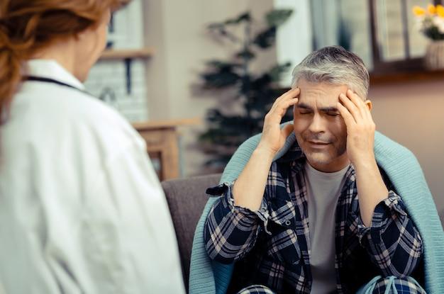 お願い助けて。強い頭痛に苦しんでいる間、医者に話している落ち込んでいる成熟した男