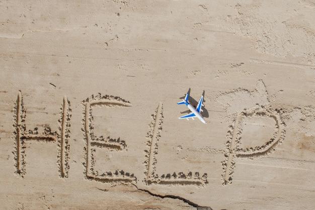 砂の上の碑文と飛行機を手伝ってください。私を助けてください。熱帯のビーチで。