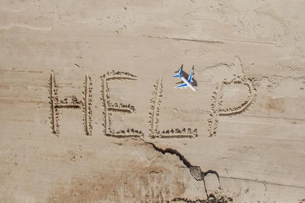 砂の上の碑文と飛行機を助けてください 助けてください 熱帯のビーチで