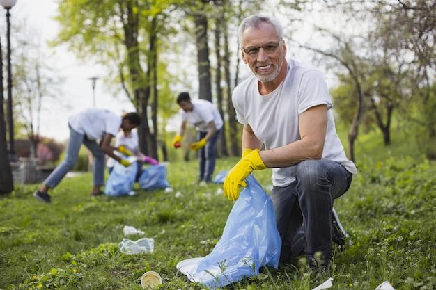 Помогите планете. оптимистичный старший волонтер держит мешок для мусора и смотрит в камеру