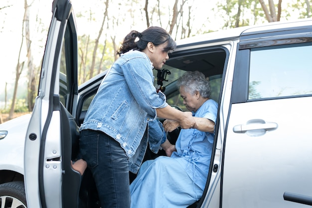 Help and support asian senior or elderly old lady woman patient get to her car