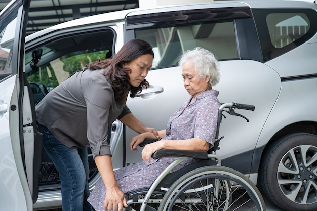 Help and support asian senior or elderly old lady woman patient prepare get to her car.