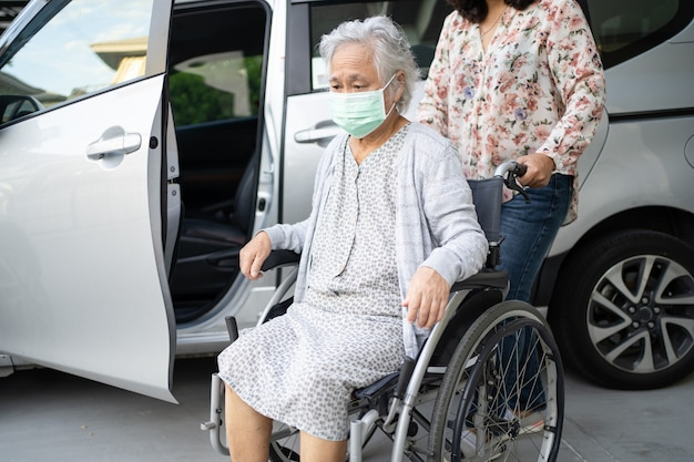 Help and support asian senior woman patient sitting on wheelchair get to her car
