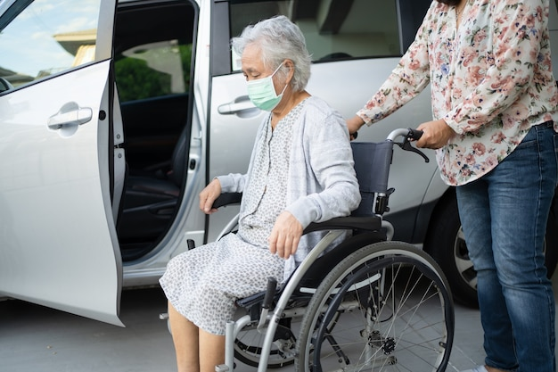 Help and support asian senior woman patient sitting on wheelchair prepare get to her car