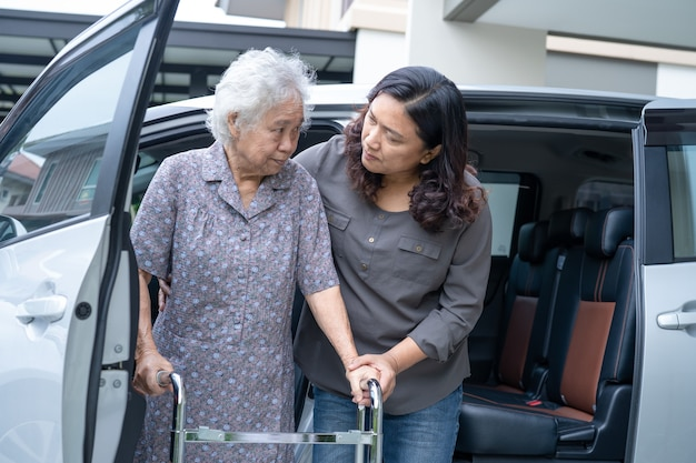 Help and support asian senior woman patient walk with walker prepare get to her car