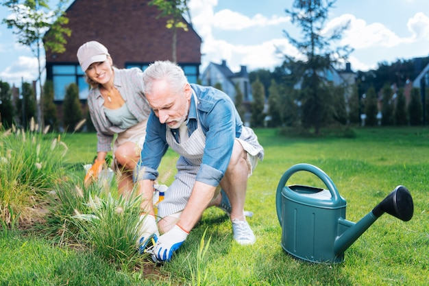 Help and support. bearded grey-haired husband supporting and helping his beautiful beaming wife in garden bed