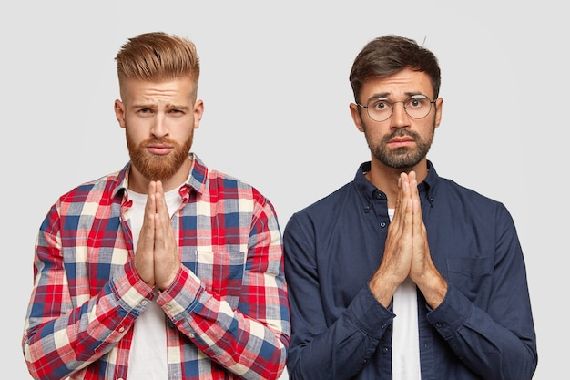 Help us one more time. two bearded friends have midserable expressions, hold hands in pray, ask for apology or forgiveness