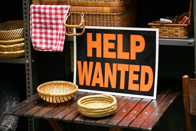 Help wanted sign displayed in a shop selling woven baskets in a job vacancy, hiring and employment concept