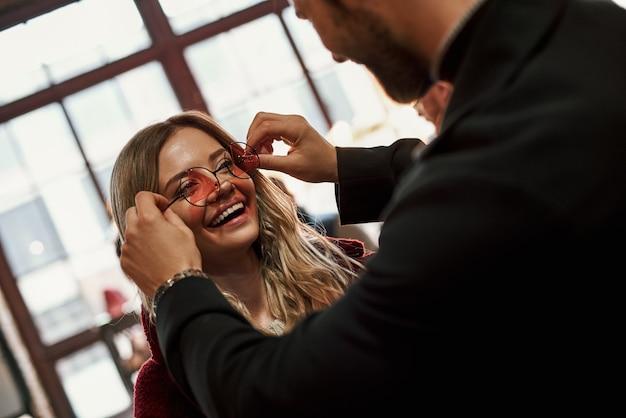 サングラスの選択を手伝ってください。小さなストリートマーケットで女性のためのサングラスを選ぶ幸せな若い楽しいカップル。若いスタイリッシュな男性は女性がサングラスをかけるのを助けます