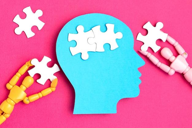 ジグソーパズルのピースが入った精神疾患のコンセプトペーパーカットヘッドを手伝ってください