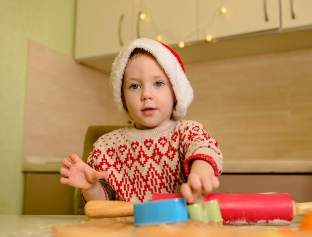 Помощник в шляпе санты и красном свитере делает печенье дома. рождество