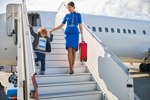Helpful airline hostess assisting a kid in exiting an aircraft
