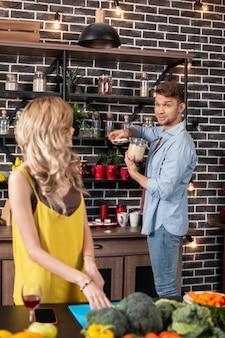 お世話になった彼氏。美しい金髪の女性が台所で料理をするのを手伝う親切な愛情のあるボーイフレンド