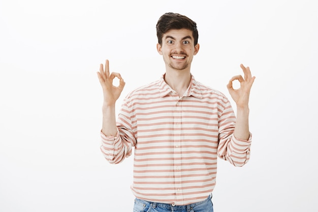 Helpful coworker ready to help. portrait of energetic friendly european man with moustache, raising hands and showing okay or great sign, approving idea and being happy to ensure friend over gray wall