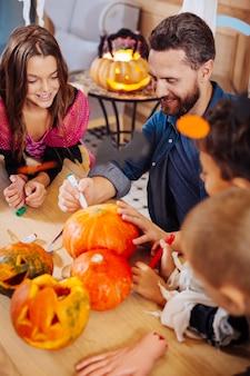 Полезный отец. бородатый отец помогает своим детям раскрашивать и вырезать тыквы для семейного празднования хэллоуина