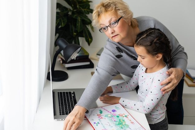 役に立つおばあちゃん。かわいい孫娘が宿題をするのを手伝ってくれる愛情のこもったおばあちゃん