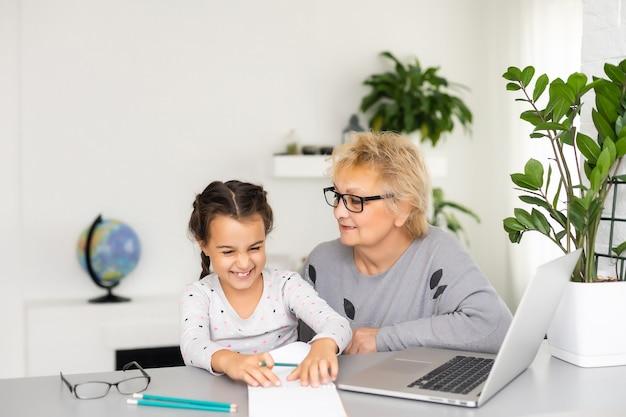 도움이 되는 할머니. 그녀의 귀여운 손녀가 숙제를 하는 것을 돕는 사랑하는 할머니