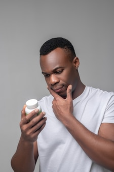Helpful information. interested thinking dark-skinned man in light tshirt looking at package of vitamins in good mood