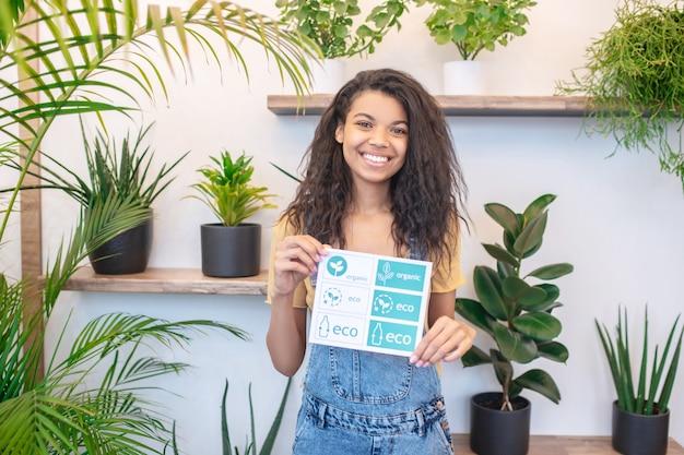 Полезная информация. молодая веселая женщина-мулатка с маленьким плакатом со здоровыми продуктами стоит в помещении среди растений