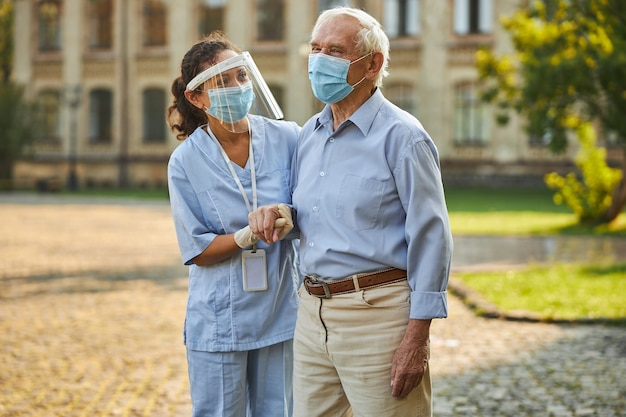 Helpful nurse aiding aged man to make steps