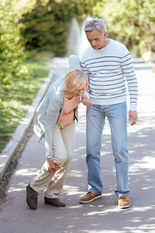 Helpful retired peaceful man caring about his aged wife and helping her to make steps while walking in the open air