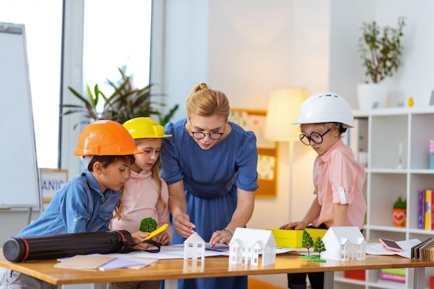 Полезный учитель. стильная учительница помогает своим ученикам в касках делать строительные эскизы на уроке