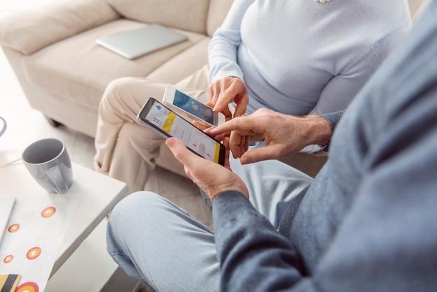 役立つ技術。居間に座って携帯電話で天気予報をチェックし、比較する老夫婦のクローズアップ