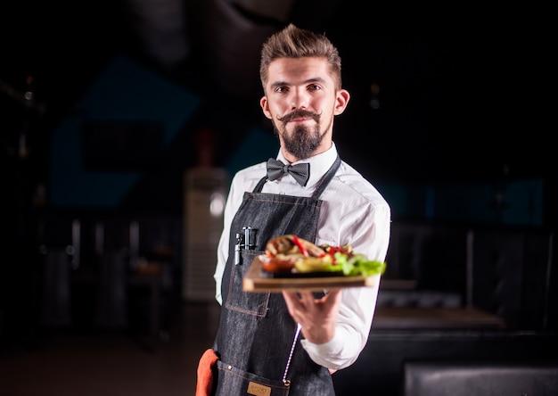 Helpful waiter helpfully serves appetizing dish in the restaurant.