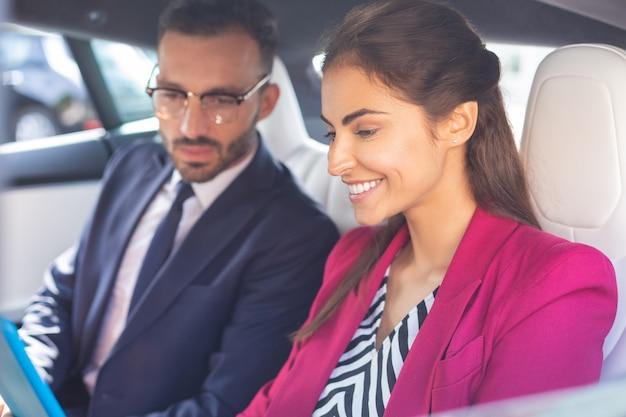 도움이 되는 아내가 웃고 있습니다. 사무실로 가는 길에 차 안에서 남편 옆에 앉아 웃고 있는 유용한 아내