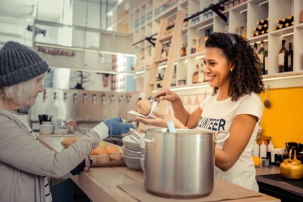 コミュニティを支援します。ボランティアセンターで働きながら食事を提供するうれしそうな若い女性