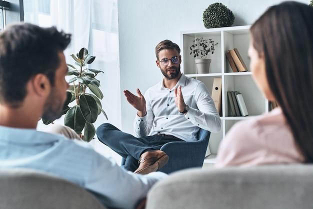 カップルを助ける。セラピーセッションに座っている間心理学者に耳を傾ける若い夫婦