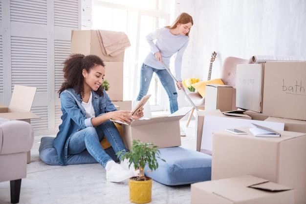 서로 돕는다. 액자 사진을보고 그녀의 룸메이트가 새로운 기숙사 방에서 바닥을 청소하는 동안 웃고 쾌활한 어린 소녀