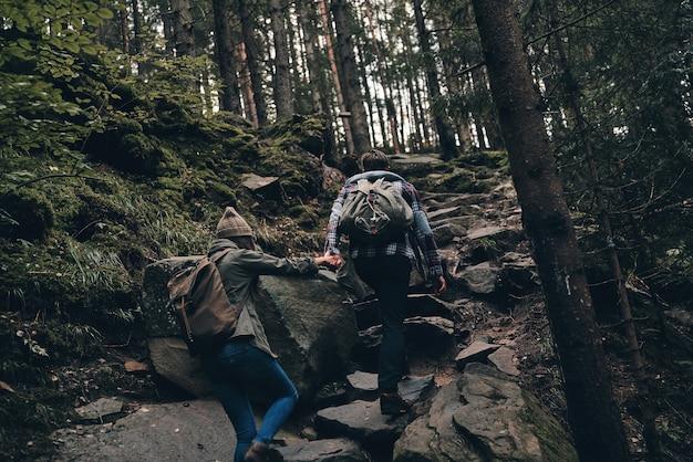 Помогая друг другу. вид сзади молодой пары, взявшись за руки во время прогулки вместе в лесу