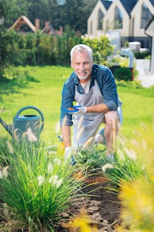 Helping in garden. handsome husband smiling broadly while feeling extremely happy helping his wife in garden