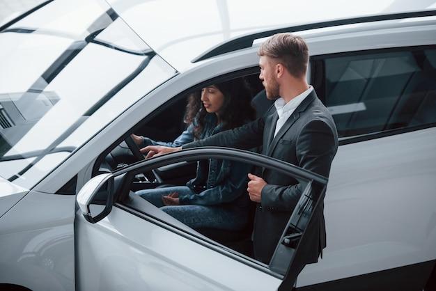 Aiutare la ragazza a decidere. cliente femminile e uomo d'affari barbuto elegante moderno nel salone dell'automobile