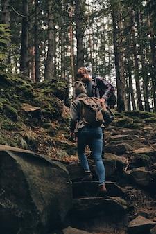 Рука помощи. молодая пара в полный рост, взявшись за руки и поднимаясь вверх, вместе путешествуя по лесу