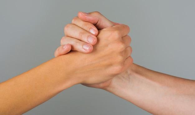 救いの手。ジェスチャー、助けと希望のしるし。お互いを取っている2つの手。人々は握手します。