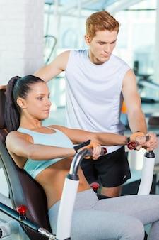 그녀의 운동을 돕습니다. 자신감 있는 강사가 그녀를 돕는 동안 체육관에서 운동하는 아름다운 젊은 여성