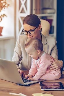 엄마를 돕습니다. 사무실에서 그녀의 어머니와 함께 사무실 책상에 앉아있는 동안 노트북을 사용하는 어린 아기 소녀