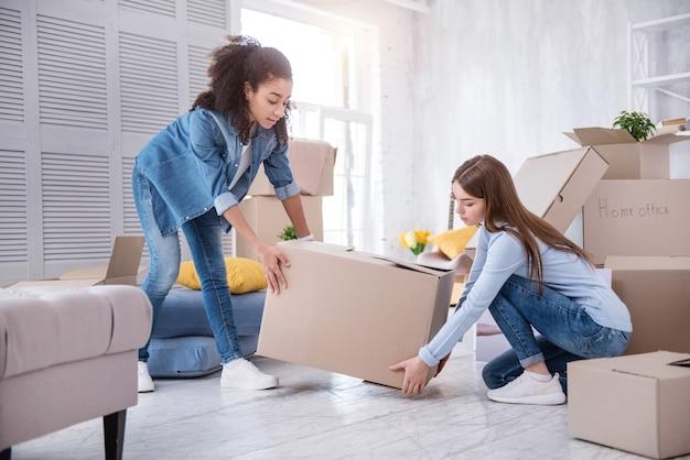 互いに助け合う。かわいらしい若い女の子がお互いに助け合い、荷物を詰めながら重い箱を一緒に持ち上げます
