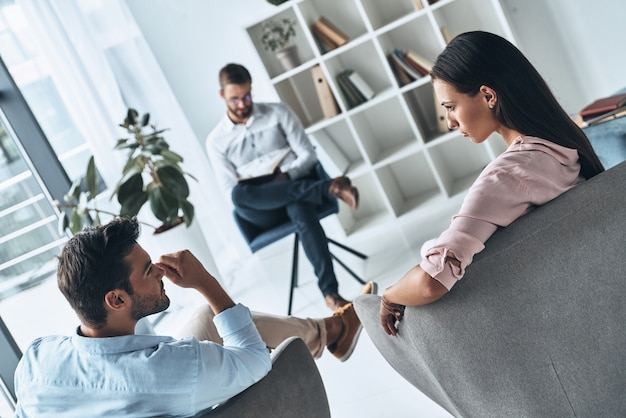 Helping others. young married couple talking while sitting on the therapy session with psychologist