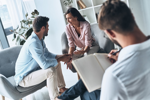 Helping people. young married couple talking while sitting on the therapy session with psychologist