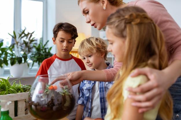 生徒を助ける。植物や花について生徒を助けるブロンドの髪の若い生態学の先生