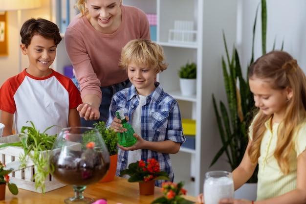 Помогаем школьникам. молодая счастливая учительница помогает своим умным ученикам поливать цветы на уроке экологии