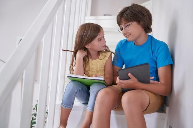 デジタルタブレットを使用して自宅の階段に座っている宿題の兄と妹を支援し、